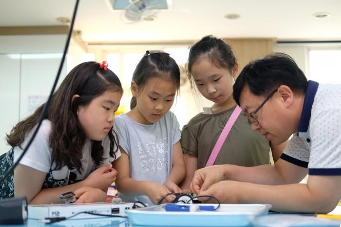 박찬 선생님이 학생들과 함께 로봇을 만드는데 집중하고 있다. - 염지현 제공